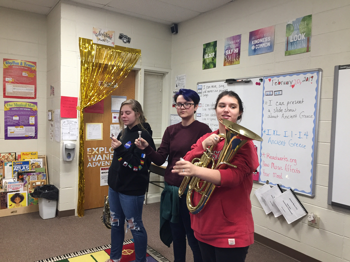 Ms. Love and band students demonstrating instruments in 6th grade music.