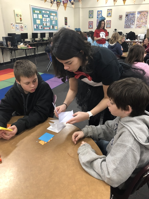 Hannah Smith helps 6th grade students with folding.